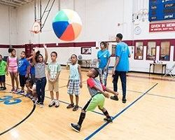 Children playing with colorful beachball on the basketball court