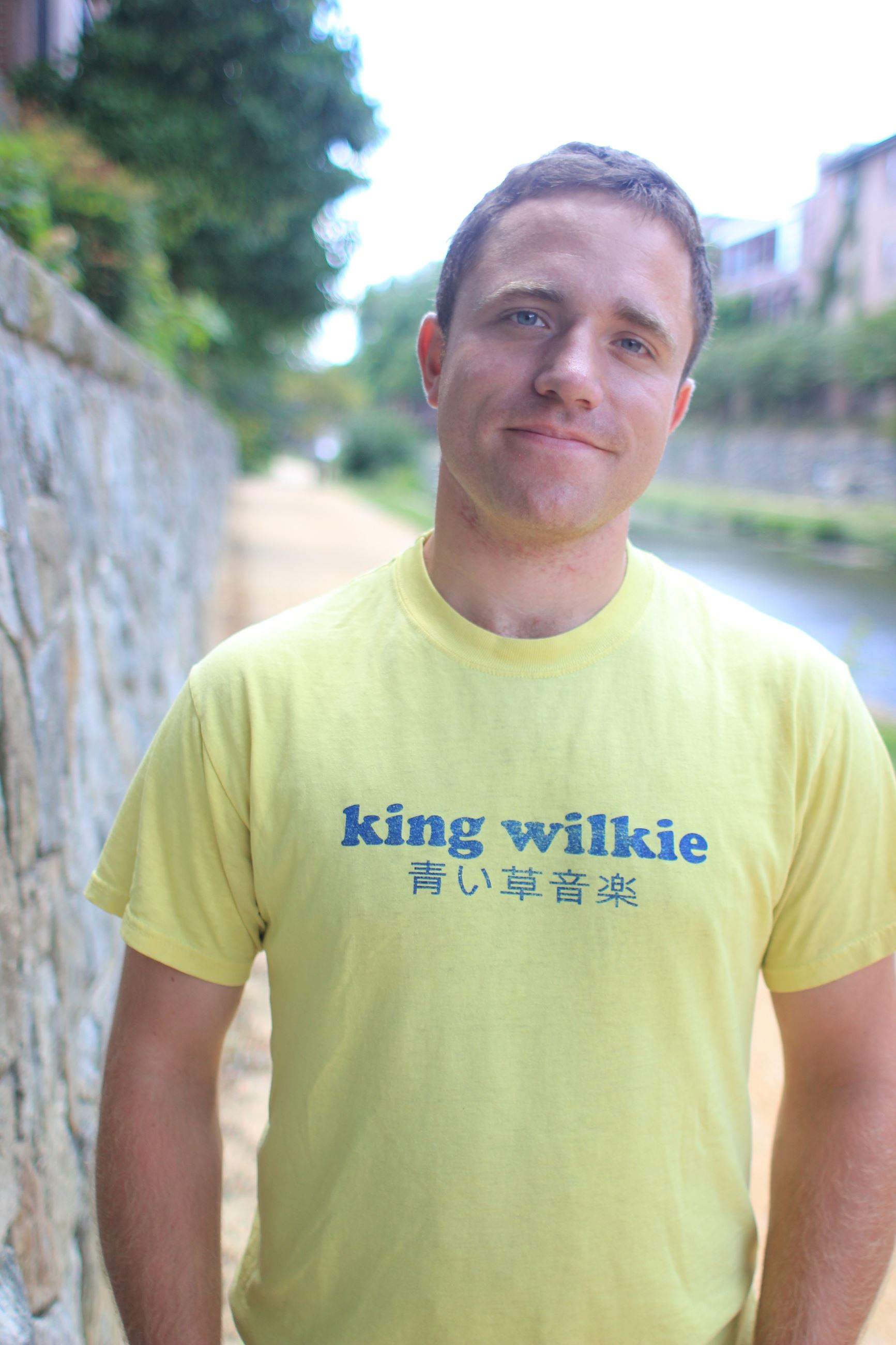 "Photo of Brent facing the camera while wearing a lemon colored t-shirt that reads ""king wilkie&#3"