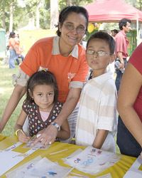 A smiling volunteer standing with two kids at a craft table.