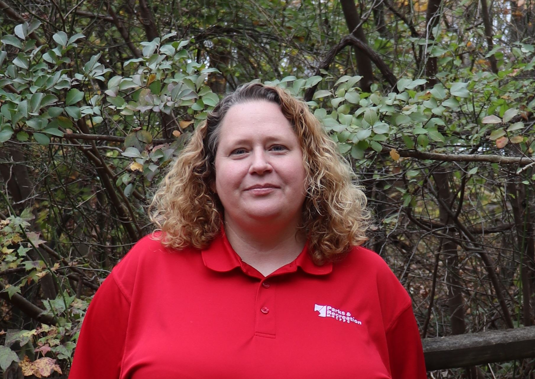 MNCPPC staff Nicole Patterson smiling and wearing a red shirt in front of a wooded background.