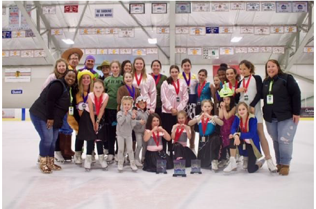 A group shot of ice skaters wearing skates on the ice of an indoor rink