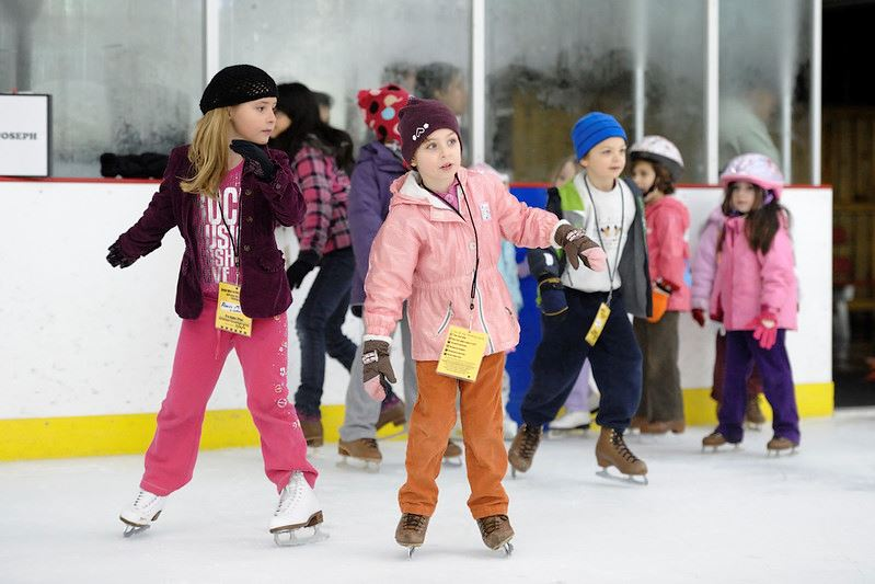 A group of children ice skating wearing brightly colored winter gear.