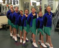 Well Ice Rink Skaters posing on a line in uniforms and skates