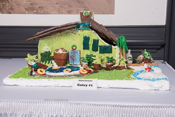 A gingerbread house decorated with green icing and colorful candies