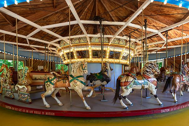 A carousel with colorful horses and benches for visitors to ride on