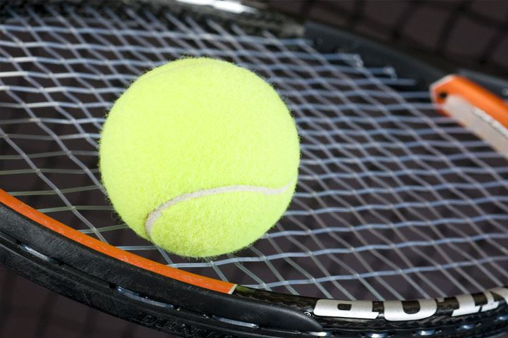 Close up of a tennis ball on a racquet