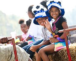 Two kids on a hayride hearing big hats smiling and waving at Kinderfest