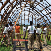 Eight people stand beneath the wooden frame of a structure they are building.