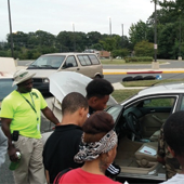 Five people stand around a car and learn how to make repairs.